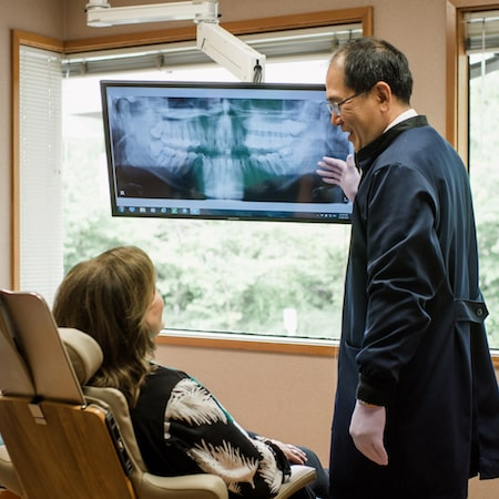Dr. Linkatoon standing an pointing to an x-ray of teeth while a female patient sits in the chair