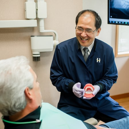 Dr. Linkatoon holding a model of teeth with braces on while speaking to an older male patient