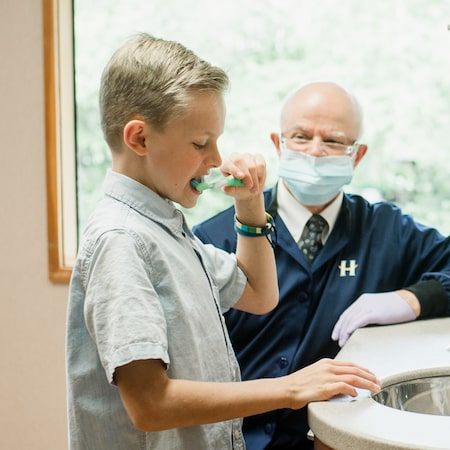 Little boy standing over the sink and brushing his teeth while Dr. Hansen evaluates