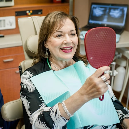 Older female patient sat in the dentist chair while looking at her smile in a hand-held mirror