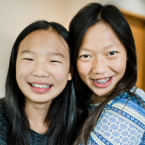 Two young girls smiling, one with braces, the other without