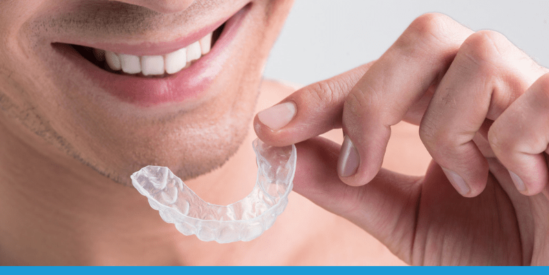Smiling man holding a clear, plastic Invisalign aligner tray.